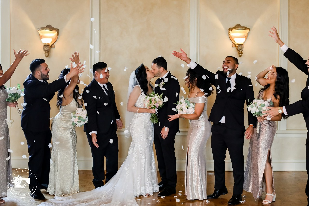bridal party throwing flowers bride and groom kissing
